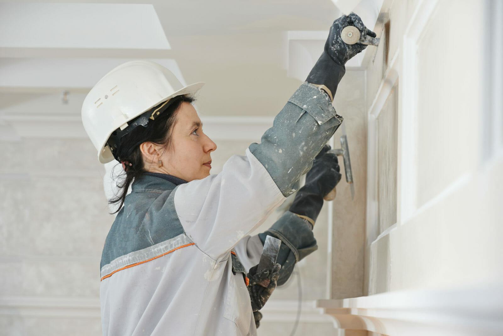 Woman restores plasterwork on wall