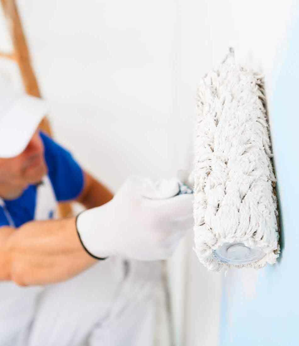 side view of  painter in white dungarees, cap and gloves painting a wall with paint roller and wooden vintage ladder, selective focus on paint roller